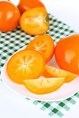 Ripe persimmons on plate close-up
