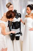 Women selecting together bridal gown and lingerie in wedding fashion store