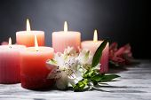 Beautiful candles with flowers on wooden table, on dark background