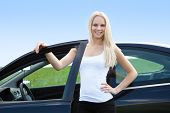Young Woman Standing In Front Of Her Car
