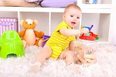 Cute little boy with toys in room