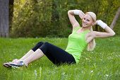 Young Blonde Woman Practicing Crunches In Park