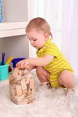 Cute little boy with wooden toy blocks in room