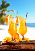 Fresh summer orange drinks, blur beach on background