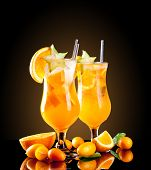 Fresh orange cocktails with fruit, isolated on black background
