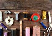 High angle shot of antique sewing tools on a rustic wooden surface. Items include, Thread, scissors,