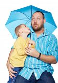 Bright studio portrait of young modern father and his small son under a blue umbrella on isolated wh