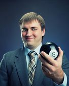 Businessman holding magic ball in his hand