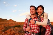 Happy couple active lifestyle hiking enjoying outdoors activity. Smiling laughing young lovers embracing looking at sunset during hike. Cheerful interracial couple, Asian woman, Caucasian man.