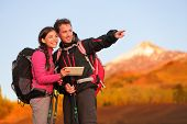 Tablet PC - hiking couple using travel app or map on hike. Man and woman hikers looking at view poin