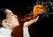 stock photo of fire-breathing  - angry gorgeus girl in the burning flame - JPG