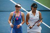 KUALA LUMPUR - APRIL 19, 2014: Zheng Saisai and Chan Yung-Jan (white dress) discuss tactics between serves in their women's semifinals of the BMW Malaysian Open tennis is Kuala Lumpur, Malaysia.