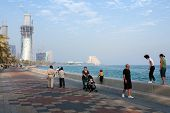 DOHA, QATAR - NOVEMBER 18, 2007: Expats and local citizens enjoy exercise on the Corniche, while bui