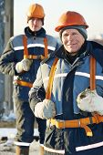 foto of millwright  - Team of builder worker in safety protective equipment at winter construction site - JPG