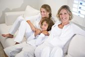 Mother and children relaxing on white sofa