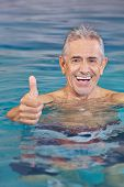 Happy old man in swimming pool holding his thumbs up