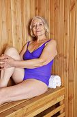 Old smiling woman sitting relaxed in a sauna