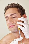 Man getting syringe with hyaluronic acid against wrinkles in the mouth area