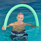 Old man in swimming pool doing aqua fitness with swim noodle