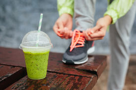 stock photo of wet feet  - Green detox smoothie cup and woman lacing running shoes before workout on rainy day - JPG