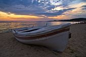 White boat on a sandy beach at sunset, west coast of Sithonia