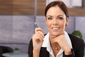 Closeup portrait of happy young businesswoman smiling in office, holding pen.