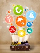 Suitcase with colorful summer icons and symbols on grungy background