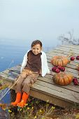 Cute little girl sitting on wooden berth near the lake in warm autumn day. Halloween pumpkins, apples and fallen leaves beside.