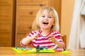 laughing llittle girl playing with plasticine at home