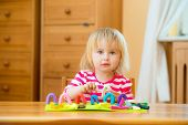 Cute Little girl playing with plasticine at home