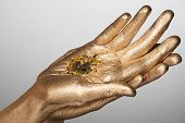 Closeup of woman hands with golden bodyart holding golden sparkles