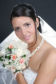 Young brunette bride posing holding a flowers bouquet