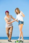 Young woman, balancing on a skateboard, assisted by her boyfriend, who holds her, helps her, and pulls her along on a bright, sunny day at the beach.