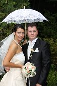 Young bride and groom couple posing holding an umbrella