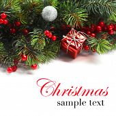 Christmas background. Christmas boarder with fir tree branch with cones and ornament. Christmas baubles in silver and red colour. Close up with copy space  and sample text. Winter holidays concept.