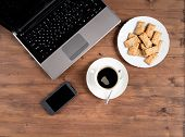 smartphone, laptop, coffee, and a plate of cookies