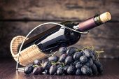 Winery Background. Bottle Of Red Wine With Cluster Of Dark Blue Grapes On Wooden Table