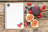 Fresh Wild Berries And Figs With Blank Notebook On Wood Background