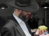 JERUSALEM, ISRAEL - SEPTEMBER 18, 2013: Traditional market before the holiday of Sukkot. The religious Jew with a long gray beard  very carefully examines ritual citrus - etrog