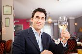 Handsome man holding a glass of white wine in a restaurant