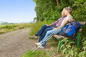 Senior couple taking a break on a bench while hiking in summer