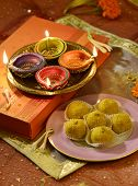 A plate full of Indian sweet, an illuminated oil lamps and a gift box- A biggest festival, Diwali still life.