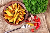 Homemade fried potato on plate, on sackcloth napkin, on wooden background
