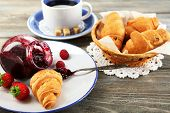 Breakfast with tea, raspberry jam and fresh croissants on wooden background