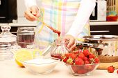 Woman cooking strawberry jam in kitchen