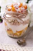 Healthy breakfast - yogurt with  fresh peach and muesli served in glass jar, on color wooden background