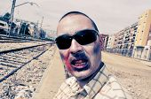 a scary zombie with sunglasses at abandoned railroad tracks, with a filter effect