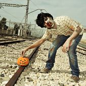 a scary zombie putting a carved pumpkin on the railroad tracks