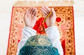 Asian Muslim woman praying on carpet with beads chain wearing traditional dress