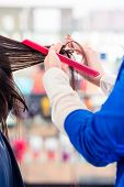 Female coiffeur cutting women hair in hairdresser shop